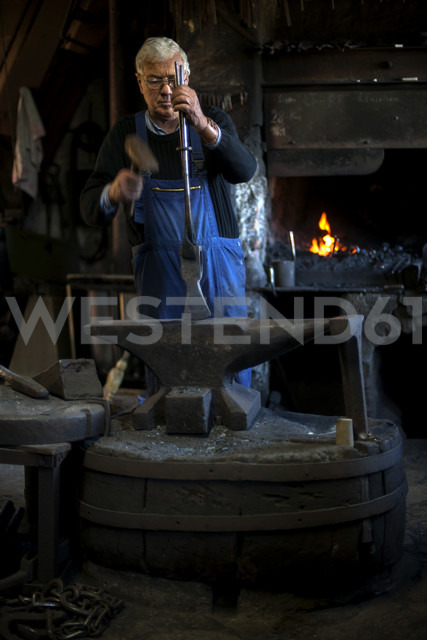 Germany, Bavaria, Josefsthal, blacksmith working on axe at historic blacksmith's shop - TCF003992 - Tom Chance/Westend61