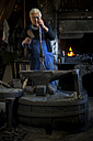 Germany, Bavaria, Josefsthal, blacksmith working on axe at historic blacksmith's shop - TCF003992