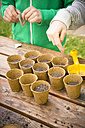Boy and girl sowing bell pepper seeds in nursery pots, partial view - LVF001134