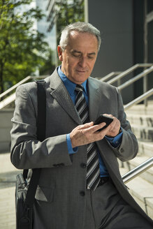 Senior businessman using cell phone outdoors - UUF000333