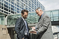 Two businessmen with digital tablet outside office building - UUF000453