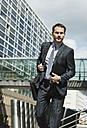 Businessman with shoulder bag outdoors - UUF000362