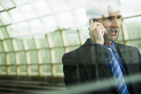 Businessman at train station on the phone - UUF000371