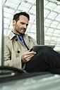 Businessman at train station using digital tablet - UUF000379