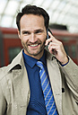 Smiling businessman at train station on the phone - UUF000380