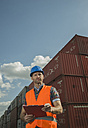 Man with clipboard wearing reflective vest at container port - UUF000411