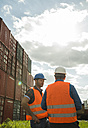 Two men with safety helmets and reflective vests talking at container port - UUF000416