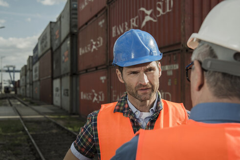 Two men with safety helmets and reflective vests talking at container port - UUF000418