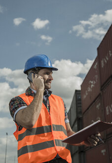 Man with clipboard on the phone at container port - UUF000422