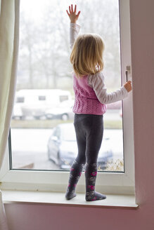 Little girl standing on window sill looking out of window - JFEF000405