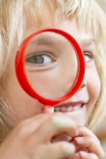 Portrait of little girl looking through magnifying glass - JFEF000335