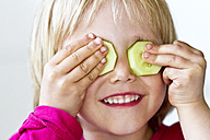 Portrait of little girl with two slices of cucumber on her eyes - JFEF000354