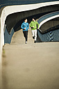 Young man and teenager running on bridge - UUF000460