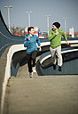 Young man and teenager running on bridge - UUF000464