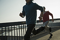 Young man and teenager running on bridge - UUF000430