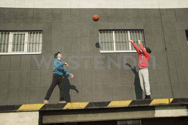 Young man and teenager playing basketball - UUF000433