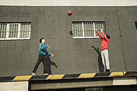 Young man and teenager playing basketball - UUF000433