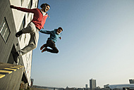 Young man and teenager jumping mid air - UUF000443