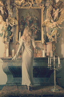 Young woman standing in front of altar, back view - FCF000154