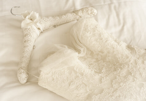 Germany, Lace wedding dress lying on bed - FCF000109