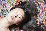 Portrait of Asian woman with closed eyes in front of colourful ground - FLF000502