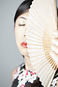Asian woman with closed eyes holding fan - FLF000506