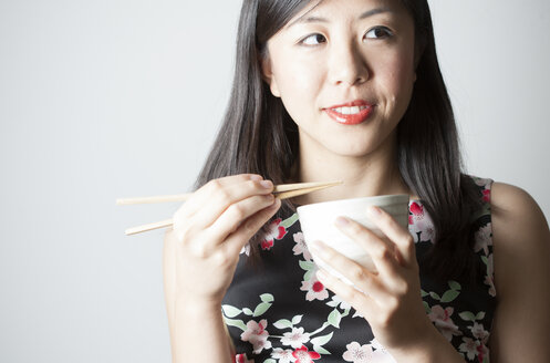 Portrait of Asian woman eating with chopsticks - FLF000510