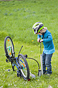 Little boy inflating bicycle tire on a meadow - MJF001091