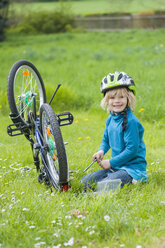 Portrait of smiling little boy repairing bicycle on meadow - MJF001083