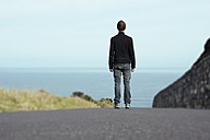 Portugal, Azores, San Miguel, man standing on street looking to the sea - ONF000473