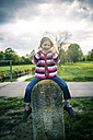 Little girl sitting on great stone with thumbs up - SARF000544