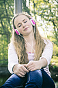 Portrait of female teenager with pink headphones daydreaming - SARF000555