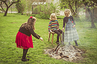 Three children with camp fire in the garden - MJF001100