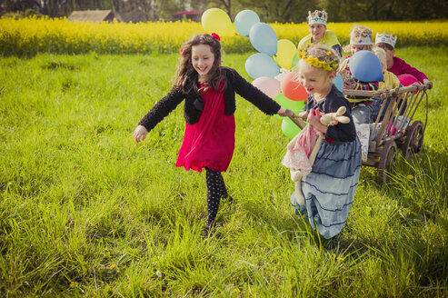 Three children on the move with wooden trolley and balloons - MJF001114