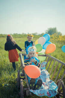 Three children on the move with wooden trolley and balloons - MJF001116