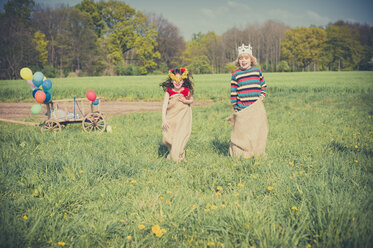 Two children sack racing on meadow - MJF001131