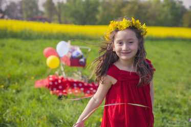 Portrait of smiling little girl wearing flowers and red summer dress - MJF001132
