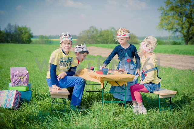 Four  children with paper crowns celebrating birthday on a meadow - MJF001143