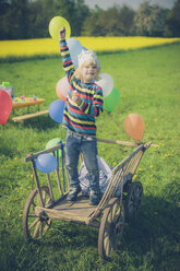 Little boy standing on wooden trolley holding ballons - MJF001144