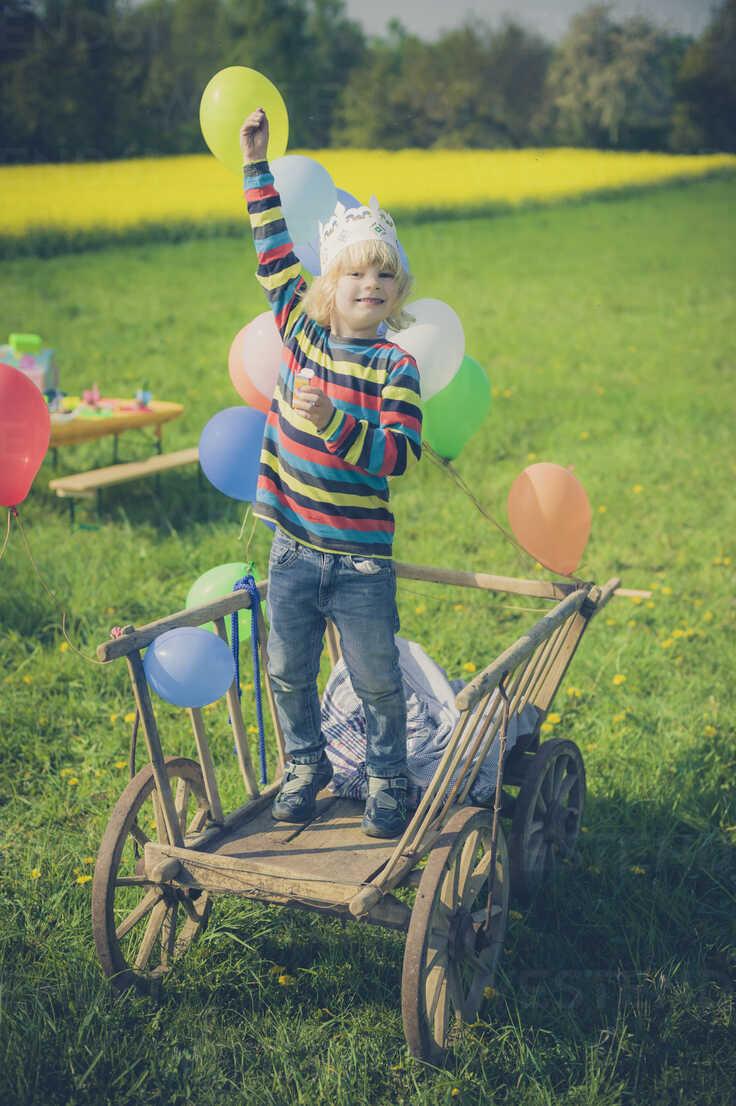 Little boy standing on wooden trolley holding ballons - MJF001144 - Jana Mänz/Westend61