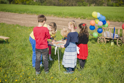 Children painting paper crowns for birthday party - MJF001148