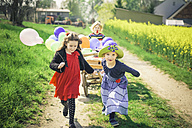 Three children on the move with wooden trolley and balloons - MJF001162