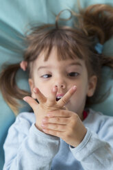 Portrait of little girl lying on bean bag counting with fingers, elevated view - LVF001158