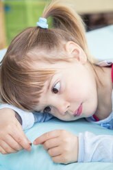 Portrait of little girl lying on bean bag - LVF001160