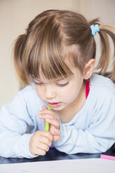 Portrait of little girl with wax crayon looking at her painting - LVF001168