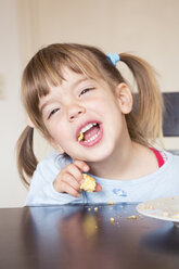 Portrait of little girl eating cake with open mouth - LVF001169