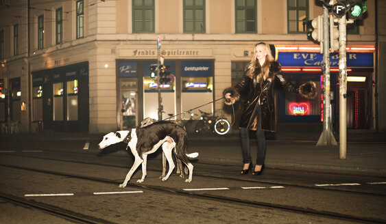Germany, Munich, Young woman walking dogs on street - FCF000168