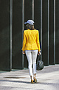 Spain,Catalunya, Barcelona, young modern woman with yellow jacket on the move, view from the back - EBSF000212