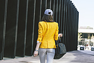 Spain,Catalunya, Barcelona, young modern woman with yellow jacket on the move, view from the back - EBSF000214