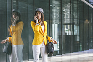 Spain,Catalunya, Barcelona, young modern woman with yellow jacket waiting - EBSF000204